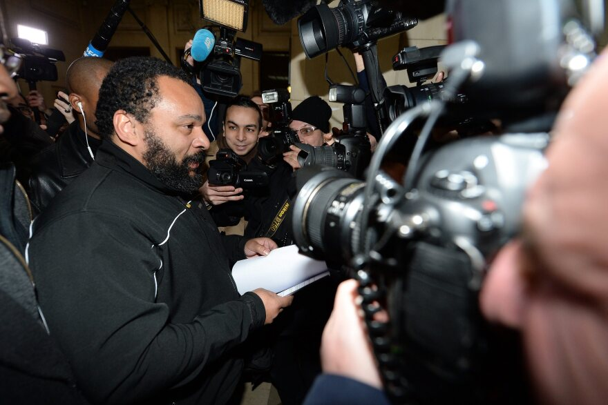 "French comedian Dieudonne M'Bala M'Bala arrives for his trial at the courthouse in Paris on Jan. 28. He goes on trial again today on charges of ""defending terrorism,"" following remarks he made on Facebook after the deadly attack on the satirical weekly <em>Charlie Hebdo</em>."