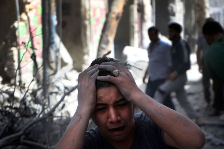 Syrian civilians are seen in the aftermath of renewed attacks on an opposition-controlled area in Aleppo on Tuesday.
