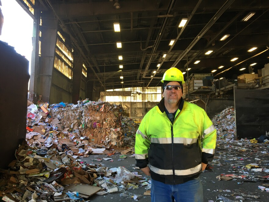 Photo of a man in a bright yellow jacket and helmet in front of piles of trash.
