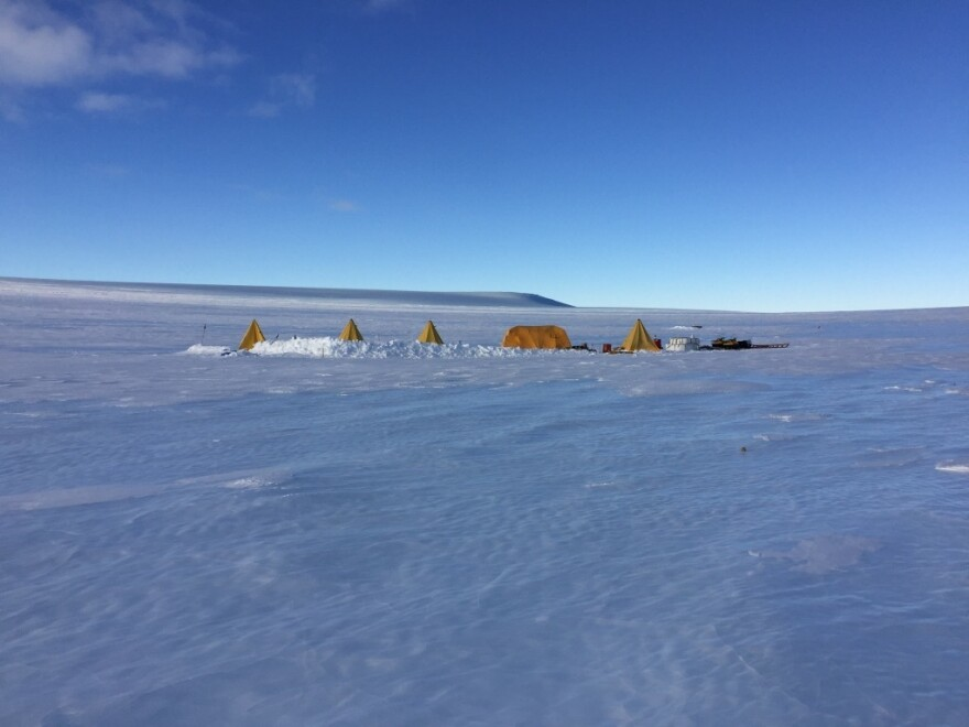 Base camp on the blue ice. Field teams of 5-8 scientists and ice core drillers spent up to 8 weeks living on the ice from Nov-Jan in 2015-2016 and 2019-2020. The smaller pyramid (Scott) tents are the sleeping quarters and a restroom while the large tent in the middle is the cook tent. Allan Hills, Antarctica, December 2015.