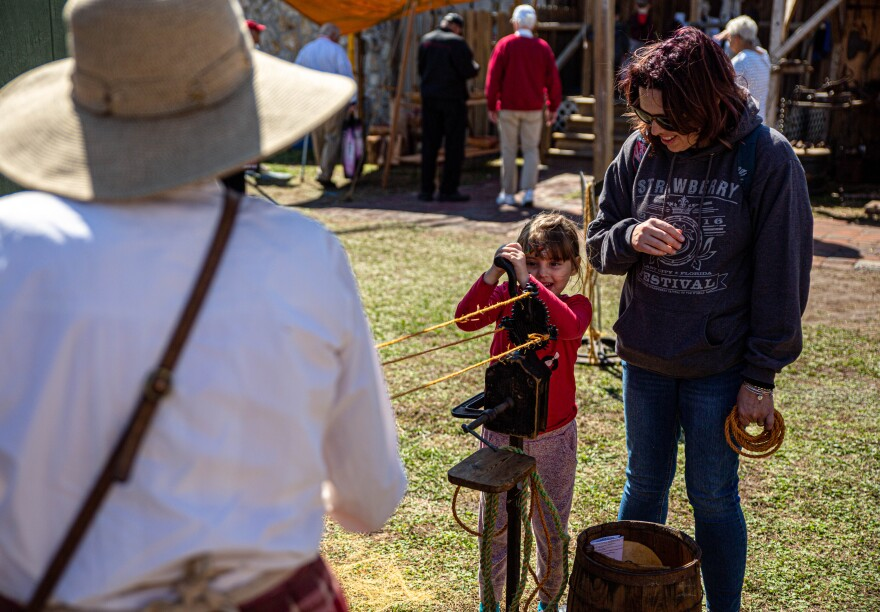 A mother and daughter pull on a rope in an interactive experience with a member of Pioneer Village.
