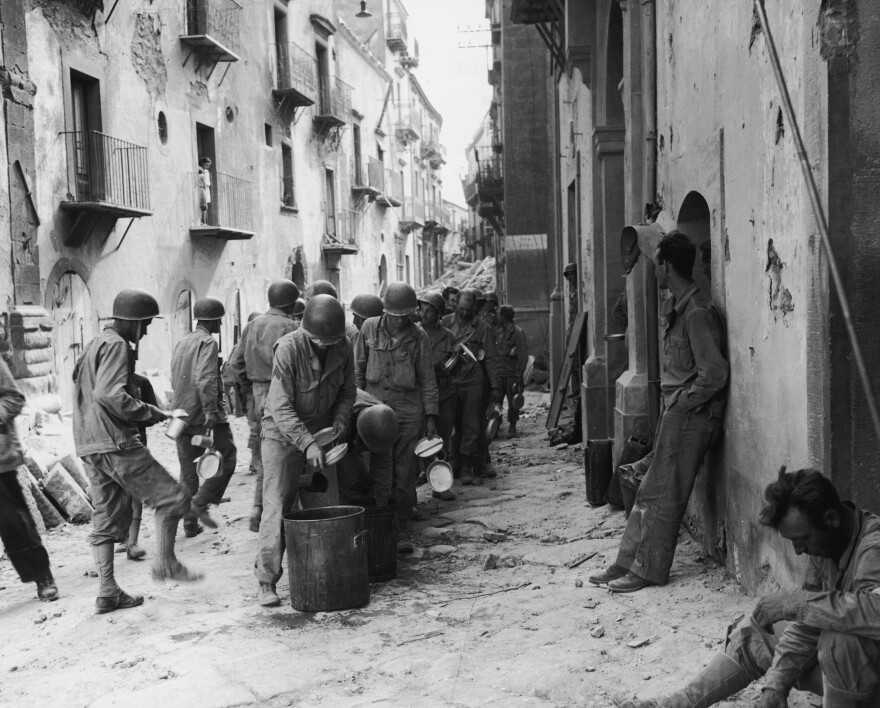 American GIs line up in the street in Troina, Sicily, utensils and dishes in hand, as they wait for a meal from a large pot, July 1943. Oregano grows abundantly in Southern Italy, where many GIs encountered the herb for the first time, and fell in love. Many brought the craving back home with them after the war.