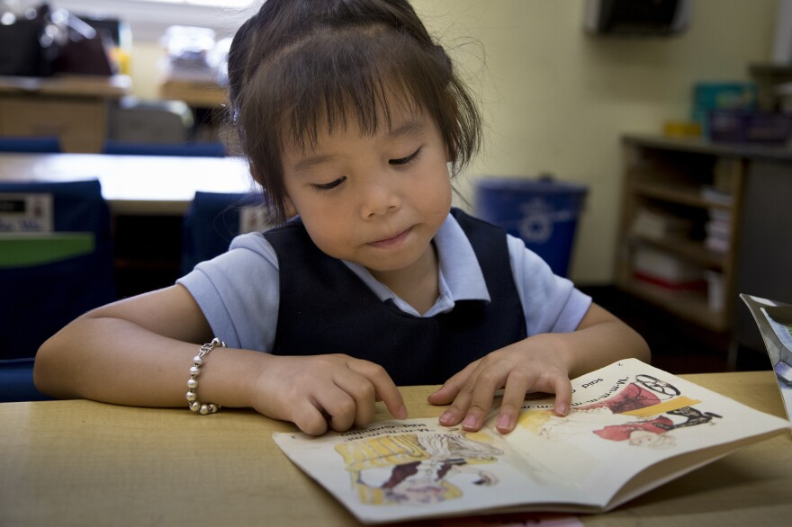 Five-year-old Vivien Huang reads a book in her kindergarten classroom. After being raised in China, her teacher says she's eagerly learning English from picture books.