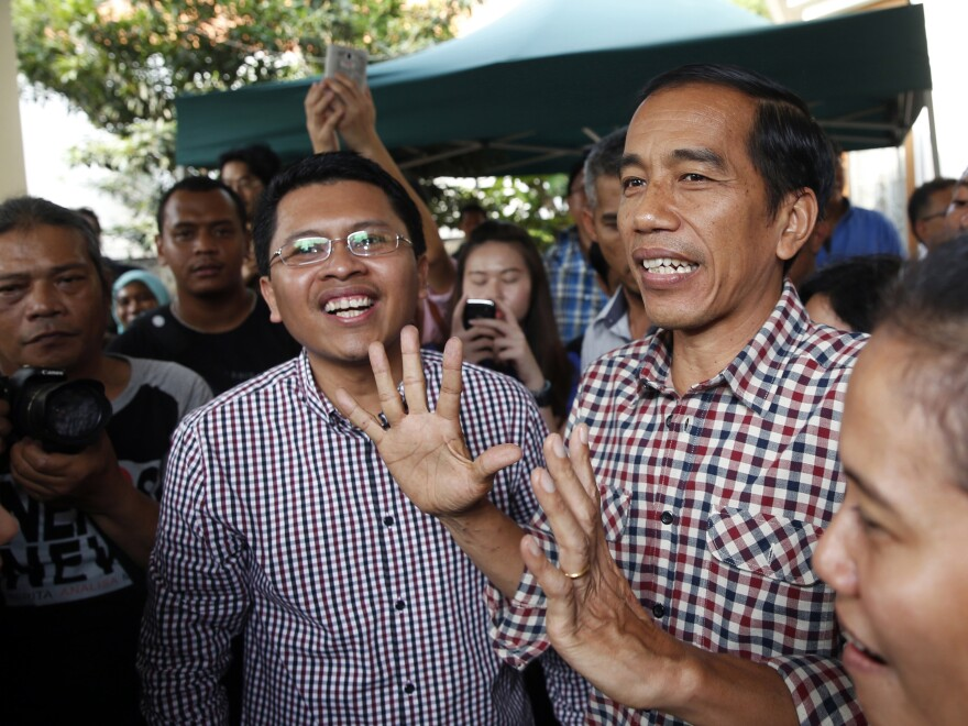 "Indonesian presidential candidate Joko ""Jokowi"" Widodo (center) holds a news conference Thursday in Jakarta. ""Quick counts"" of the election results give Widodo a narrow lead over his rival."