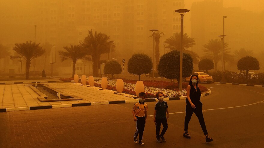 A woman and two children wear medical masks as they cross a street amid a sandstorm in Dubai.