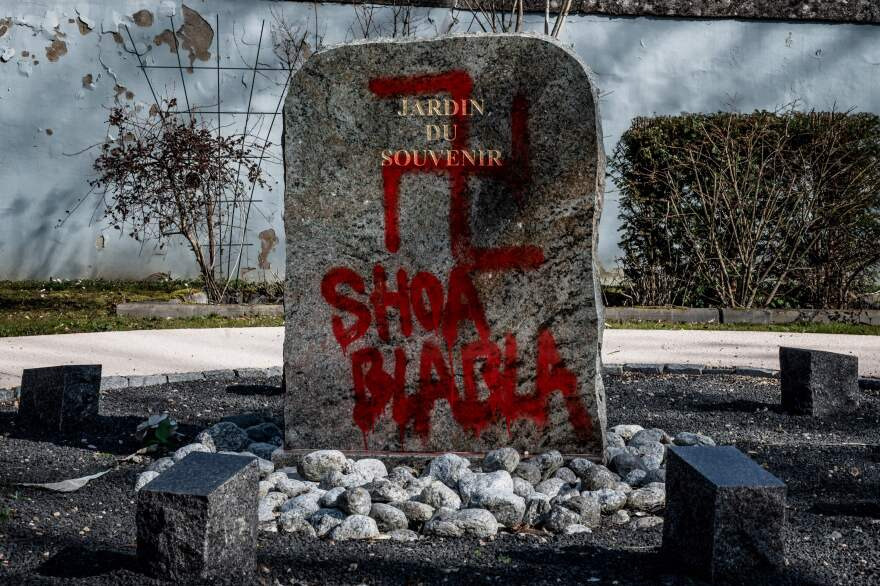 In this Feb. 20 photograph, a Nazi sign and words mocking the Holocaust were painted on a tombstone at the Garden of Remembrance in the cemetery in Champagne-au-Mont-d'Or, near Lyon, France.