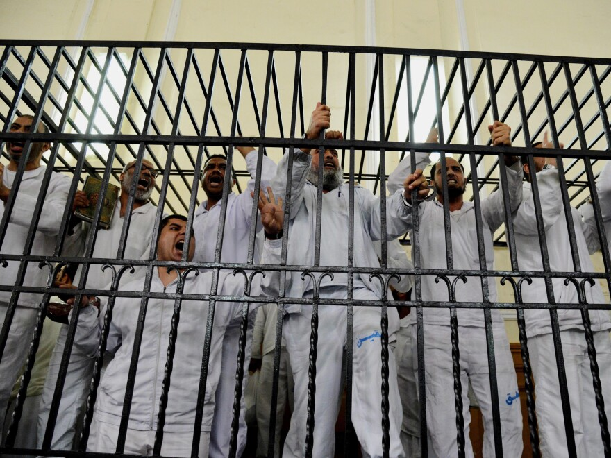 Supporters of Egypt's ousted President Mohammed Morsi, a Muslim Brotherhood leader, chant slogans against the Egyptian military during a trial in which they were charged with violence in Alexandria, Egypt, on March 29, 2014. Thousands of Muslim Brotherhood supporters have been jailed by the current government. A former prisoner tells NPR he saw some turn to ISIS in prison.