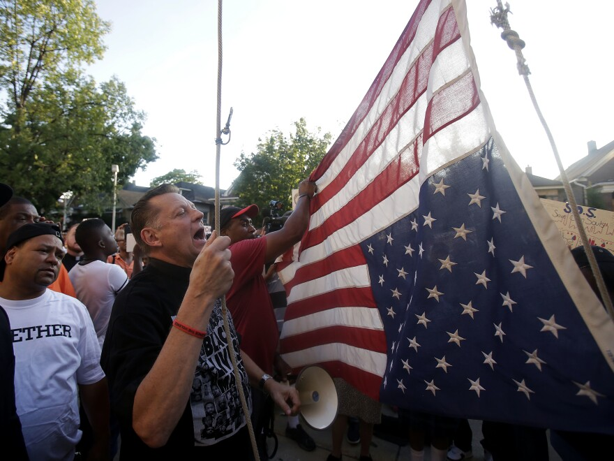 Father Michael Pfleger of St. Sabina Church hangs the American flag upside down outside his church Aug. 31 as demonstrators protest the uptick in homicides across Chicago. Thirteen people were fatally shot over the weekend, bringing the city's annual toll to at least 500.