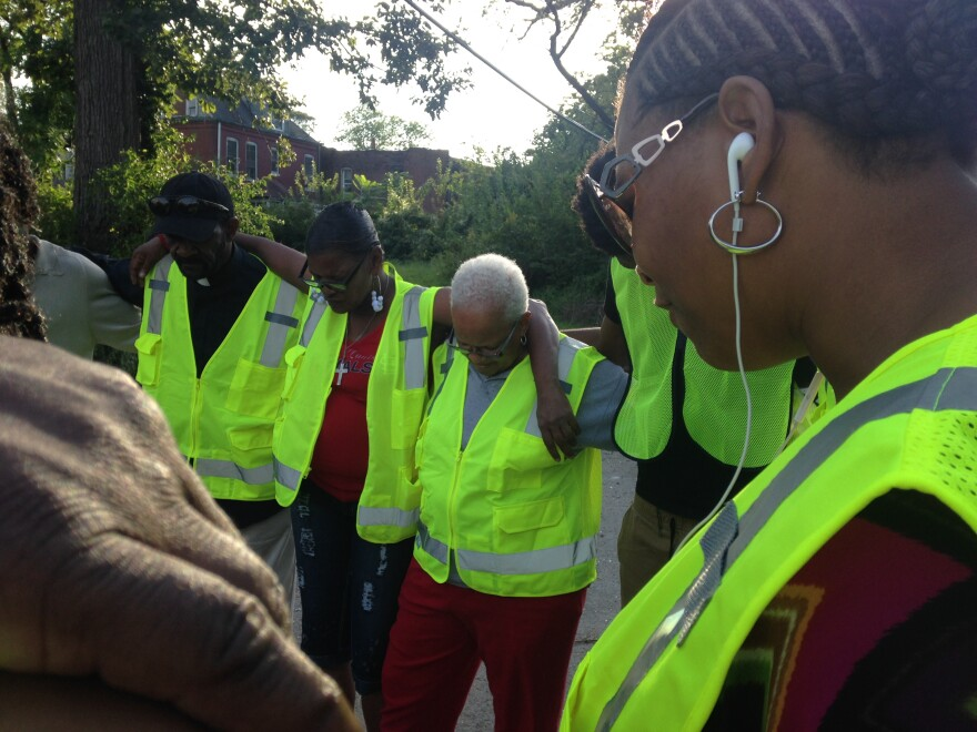 Reverend Jennifer James, left, leads a prayer with residents and the NightLIFE group during a walk on Monday evening. James works with Restoration House Community Church in Hazelwood.
