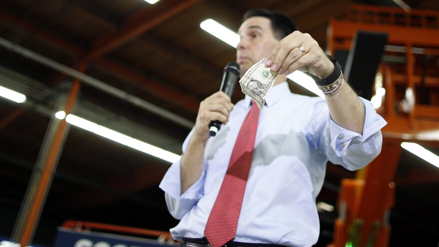 Gov. Scott Walker, R-Wis., holds up a $1 bill during a town hall in Las Vegas where he announced his plan to take on labor unions.