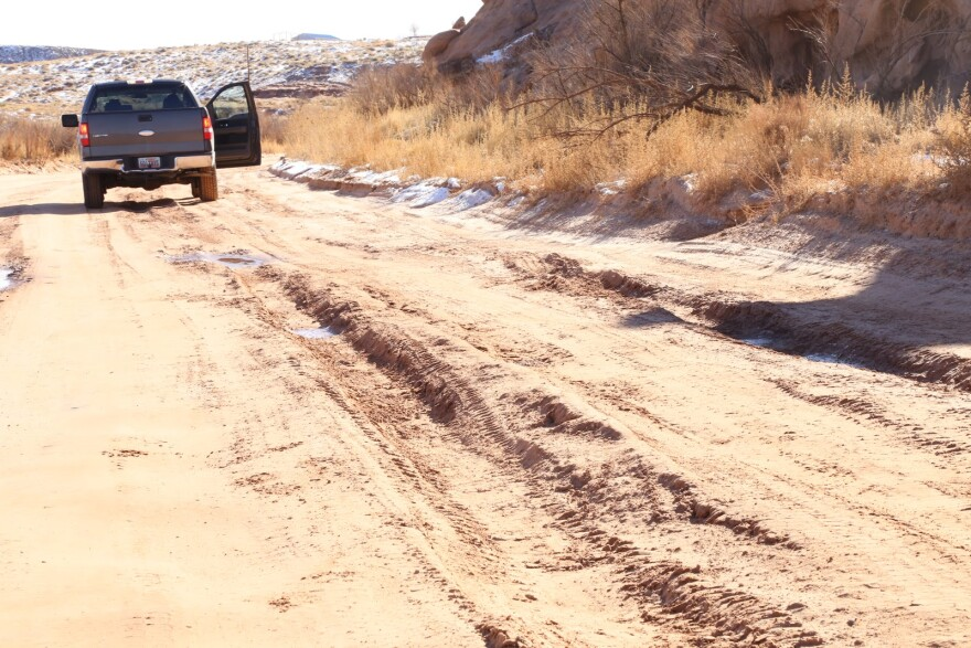 A red dirt road with deep tire ruts.