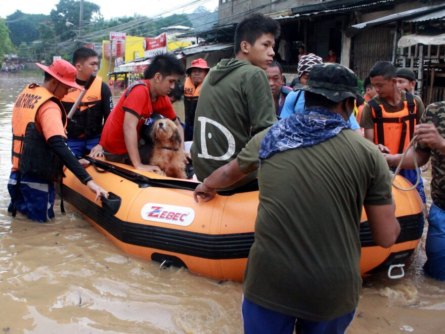 Philippine Air Force troops use a rubber boat to evacuate residents from floods in Cagayan de Oro City, southern Philippines earlier today (Dec. 4).