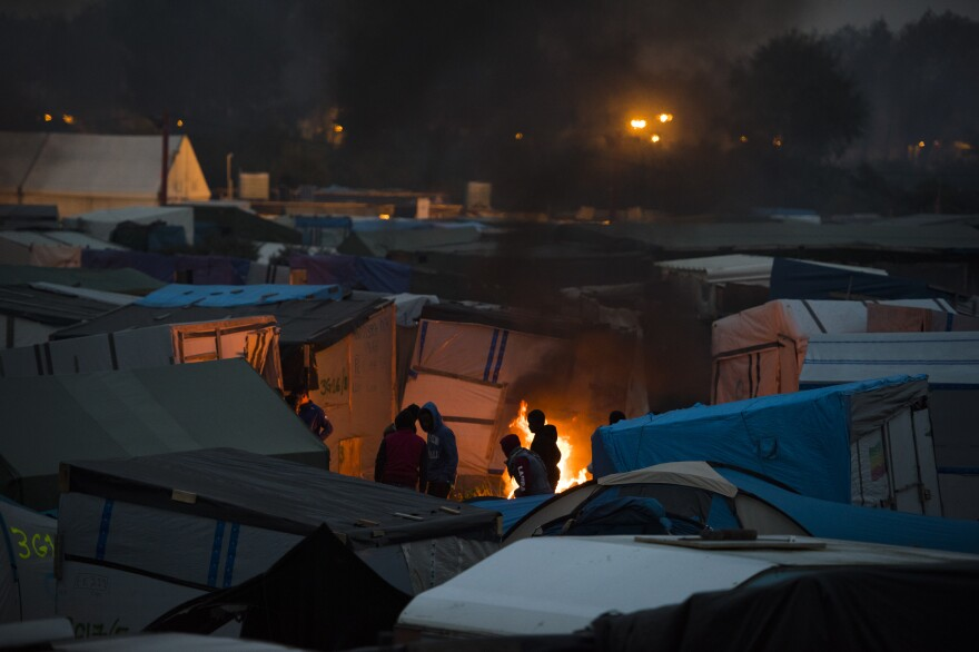 Migrants congregate around a bonfire at The Jungle on Monday evening, after evictions had concluded for the day.