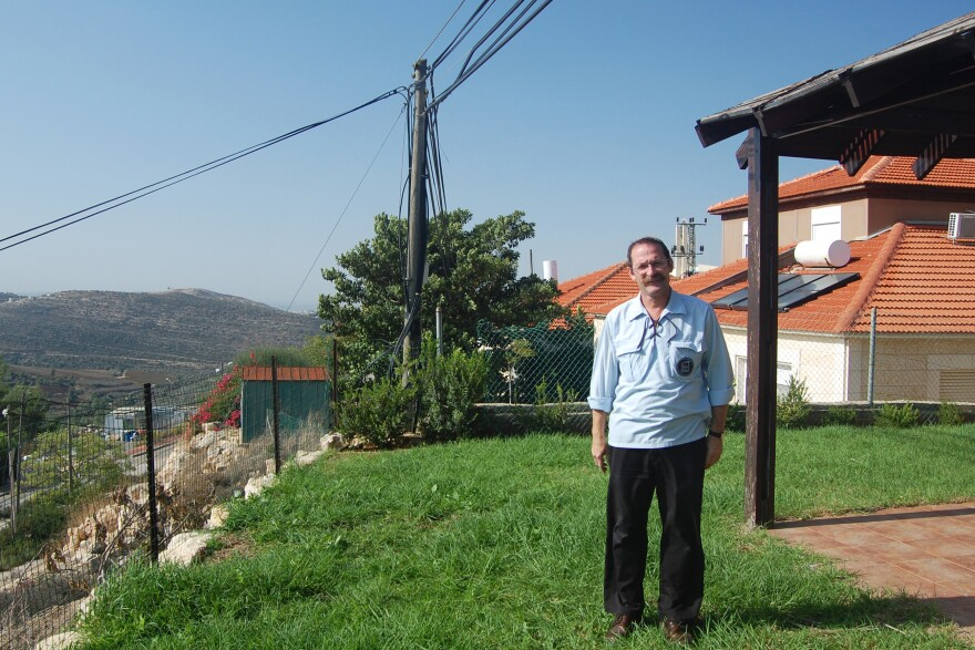 Danny Hirshberg, standing outside his home in a West Bank settlement, disagreed with Rabin's policies but helped organize this year's gathering in his memory.
