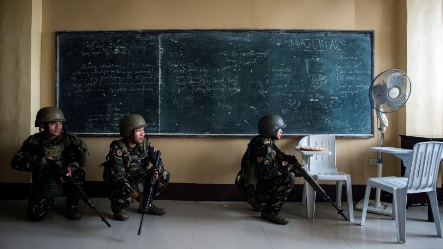 Philippine army Scout Rangers crouch in a classroom during a mission to flush out militant snipers in Marawi on Tuesday. Using these snipers, human shields and their knowledge of the city, the ISIS-linked militants have continued to maintain their grasp on parts of the city.