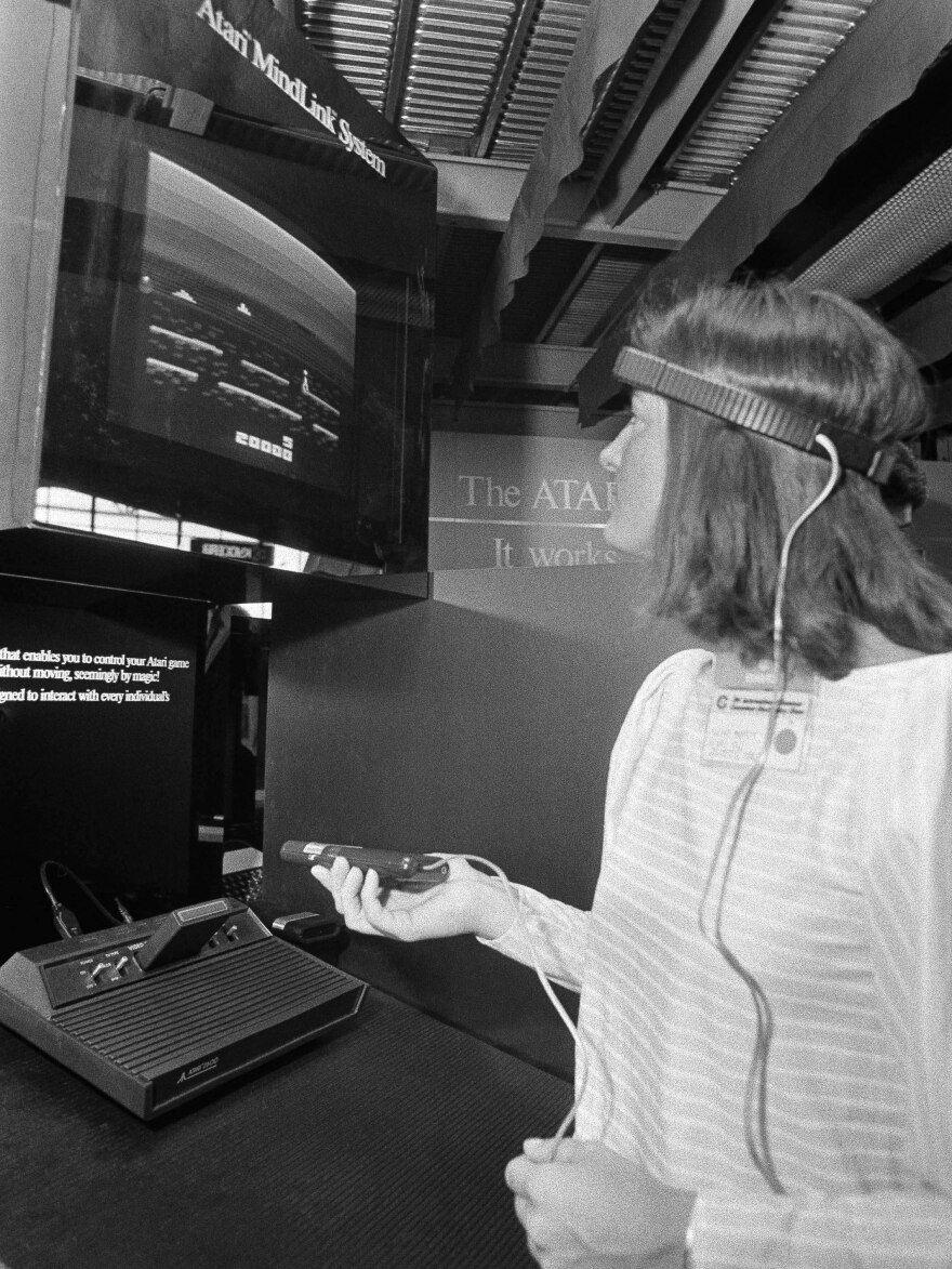 "The ""Atari Dump"" of New Mexico, where the game company rid itself of unsold game cartridges, will be excavated this summer. Here, a file photo shows a woman demonstrating Atari's unreleased 1984 Mindlink device, using a headband that picks up impulses from movement of the player's forehead."