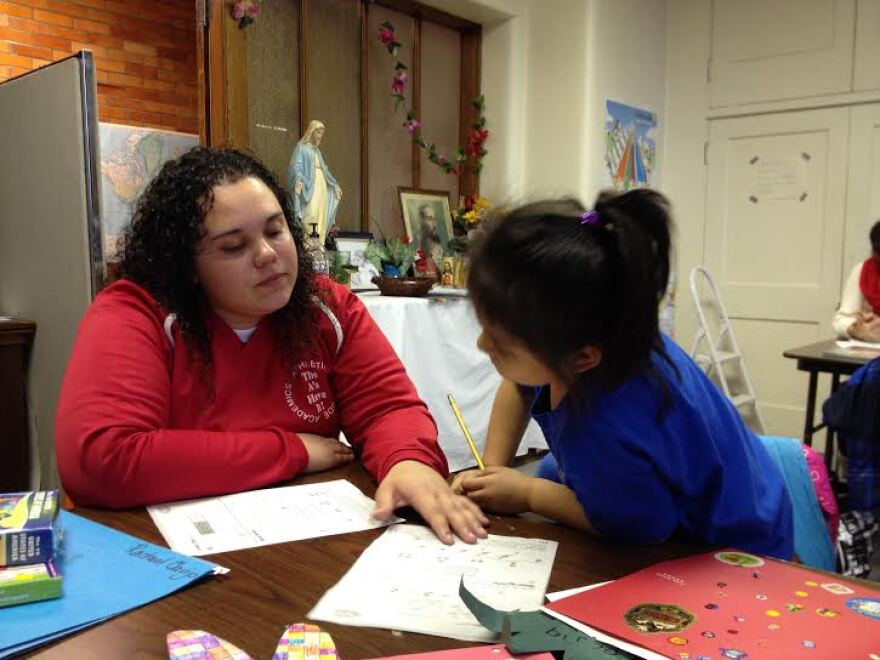 El Puente tutor, Shanel Melendez helps young student to sound out words as they read together.