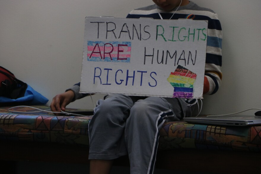 """Boy holds sign that reads, """"Trans Rights Are Human Rights."""" Symbol of a fist pumping up to the sky is on the poster."""