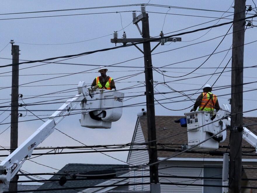 Utility crews work on power lines as dusk falls in Ship Bottom, a community on Long Beach Island, N.J.