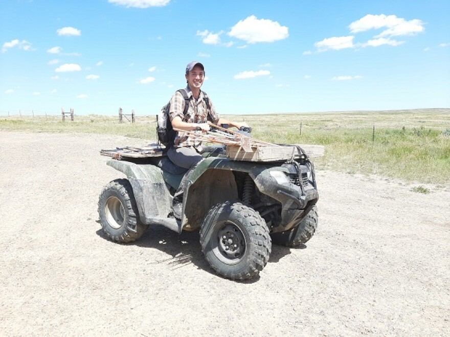 Man sitting on an ATV on a dirt road.