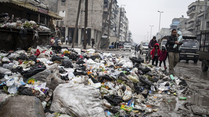 A family crosses a street piled with rubbish in Aleppo, Syria, on Jan. 5.