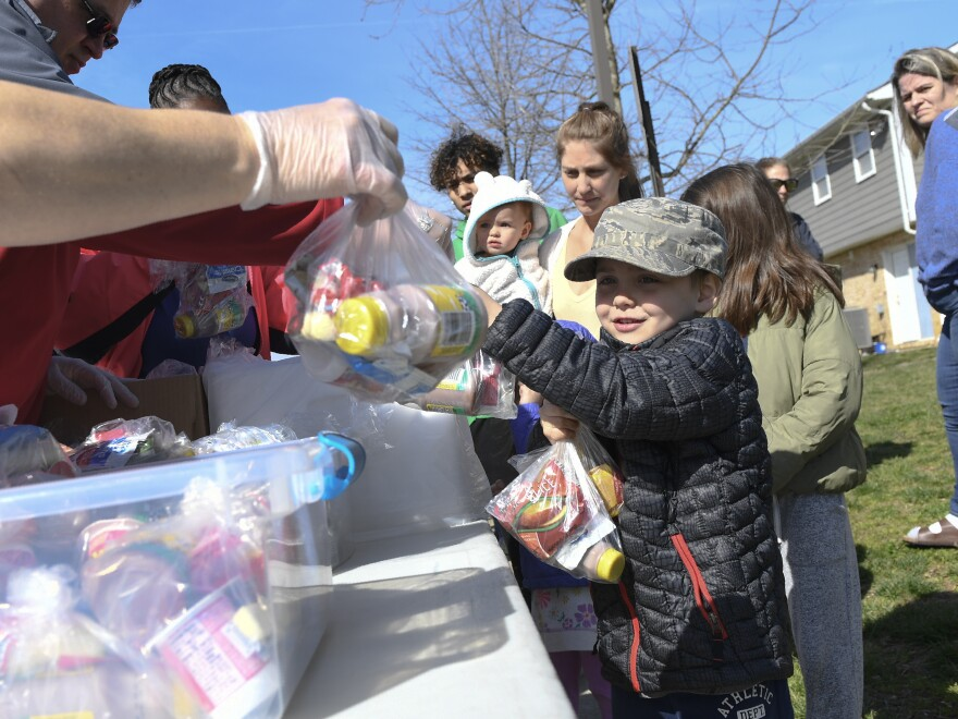 "Kids whose schools are shut down in Anne Arundel County, Md., receive food in Annapolis as part of a program to ease the burden of feeding students while schools are closed because of the coronavirus. President Trump told Americans to ""engage in schooling from home when possible"" on Monday."