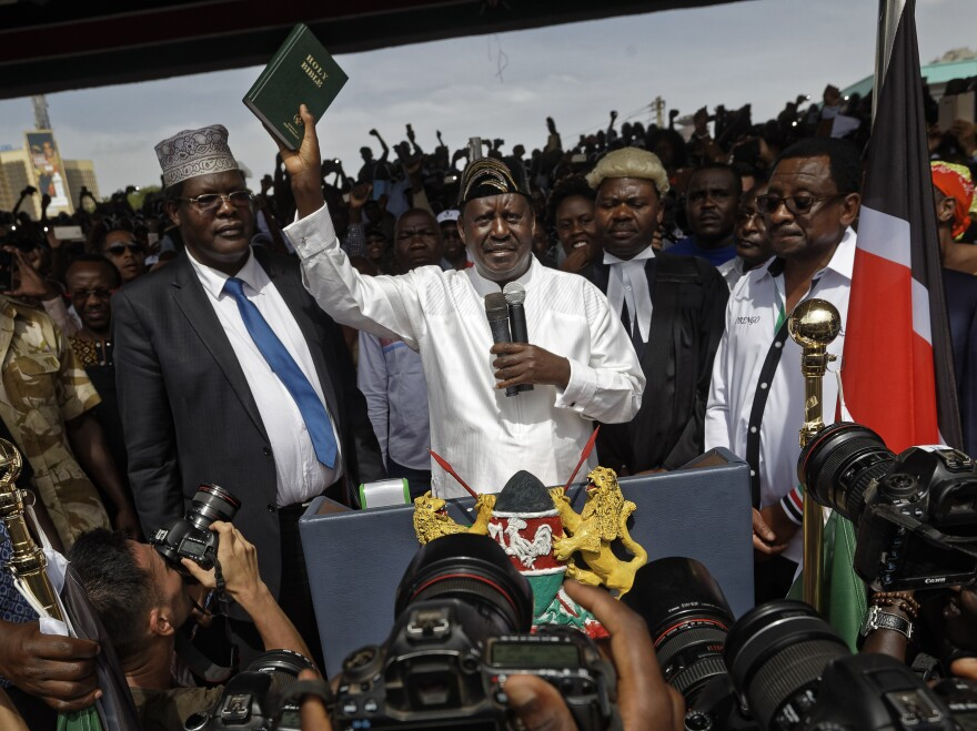"Opposition leader Raila Odinga holds up a bible, center, accompanied by lawyers Miguna Miguna, center-left, Tom ""T.J."" Kajwang, center-right, and politician James Orengo, right, after taking an unauthorized oath of office in Uhuru Park in downtown Nairobi, Kenya."
