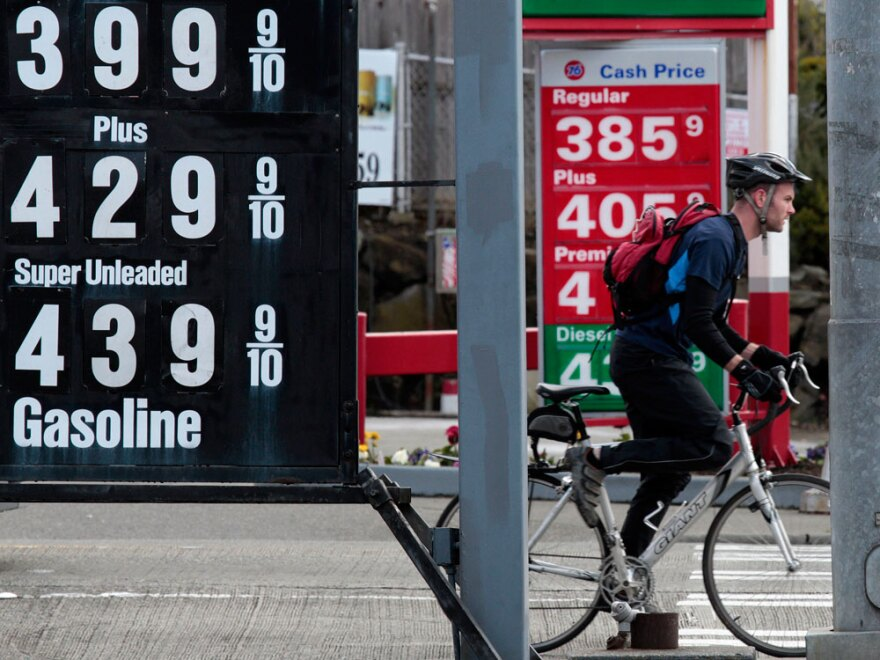 A bicyclist waits at an intersection between competing gas stations and multiple posted gas prices on Monday in Seattle.