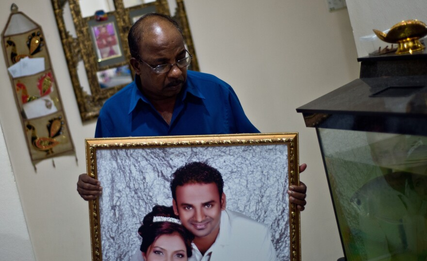 Subramaniam Gurusamy holds a portrait of his son Puspanathan, who was onboard the missing Malaysia Airlines flight, on Friday in his home in Teluk Panglima Garang, outside Kuala Lumpur.