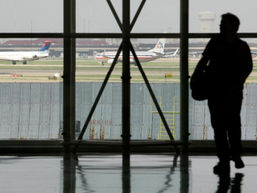 A traveler is seen in Terminal C at Dallas Fort Worth International Airport as aircraft taxi along a runway in Grapevine, Texas.