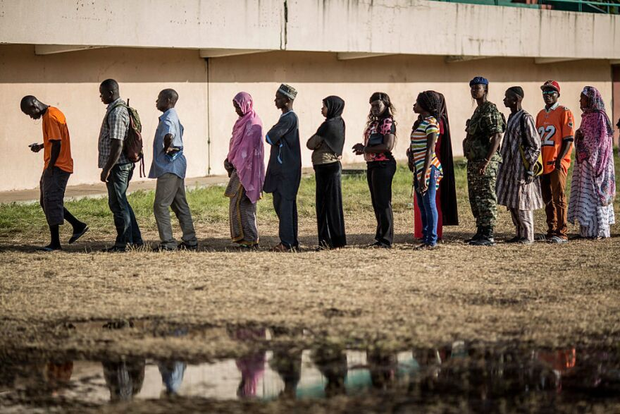 Voters queue at a polling station in Banjul during elections that pose the strongest challenge yet to the current president's 22-year rule.