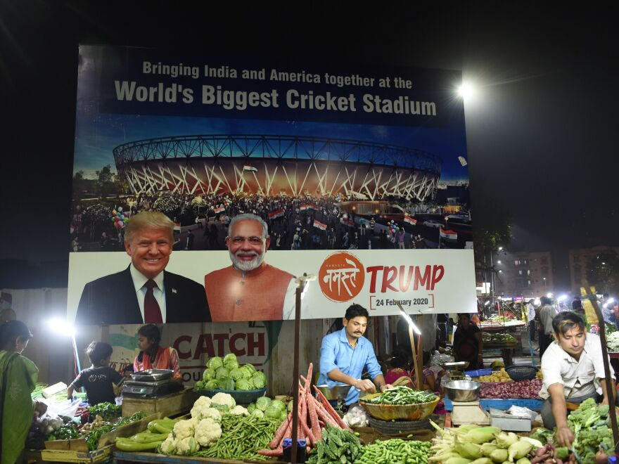 Vegetable vendors wait for customers below a billboard showing President Trump and Indian Prime Minister Narendra Modi, with the Sardar Patel Stadium in the background, on the outskirts of Ahmedabad on Feb. 19.