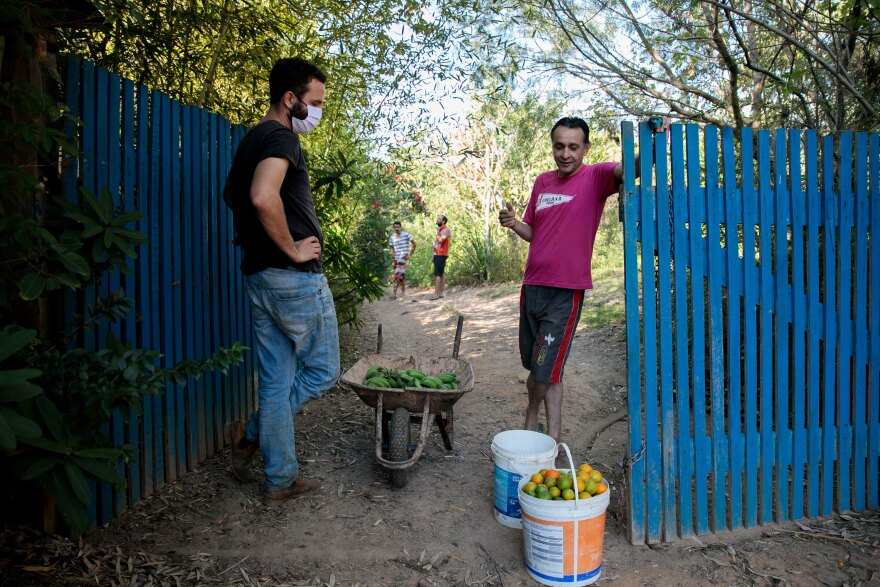 Rafael Duckur (left) stops by José Dresler Neto's farm to pick up oranges, bananas and a few avocados. Unsold produce often goes to waste; Duckur wants to bring the surplus to those who need it.