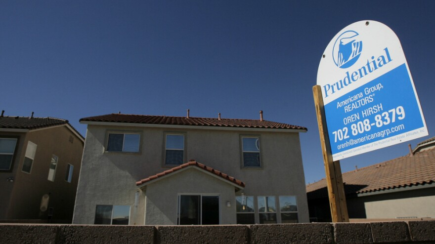 A real estate sign stands outside a home in Las Vegas. Banks are repossessing record numbers of homes in the city, but there's a flip side: It has put homeownership within reach for many low-income buyers.