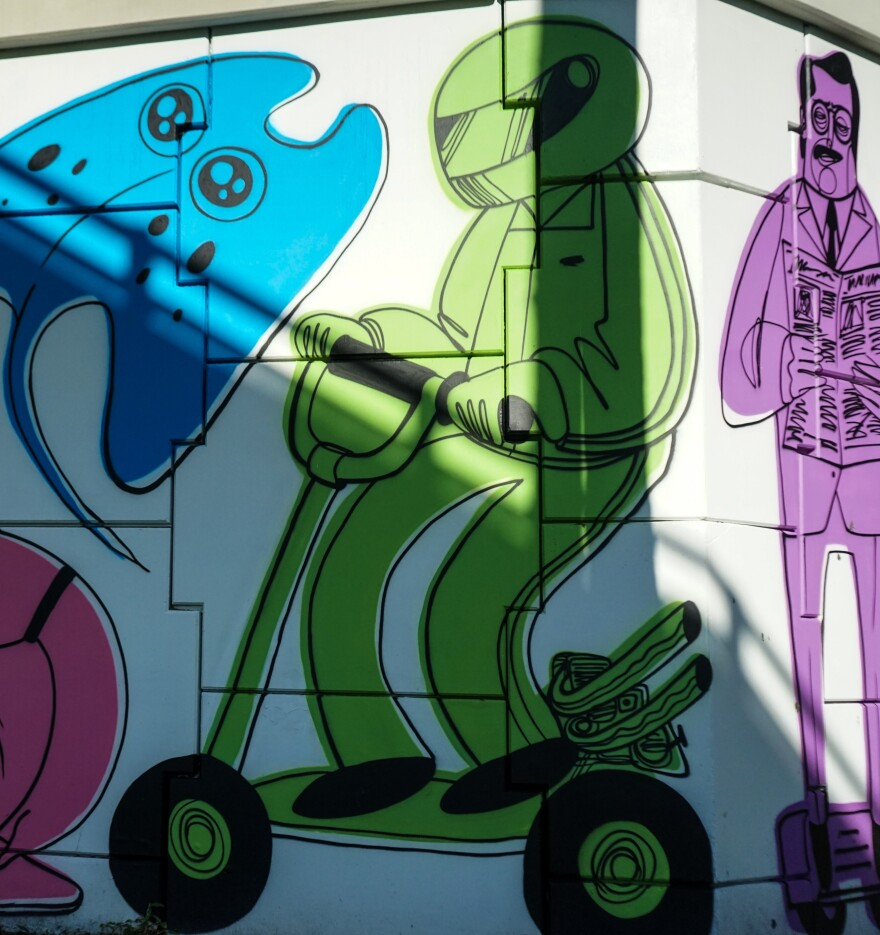 In Palladino's mural, you will find many different figures on all kinds of transportation, like this astronaut on an electric scooter.