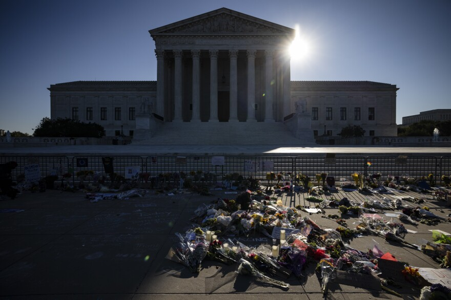 People place flowers at a makeshift memorial to honor Supreme Court Justice Ruth Bader Ginsburg in front of the Supreme Court on Sunday.