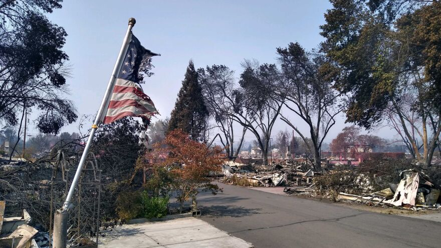 A partially burned American flag flutters in the breeze in front of the remains of a mobile home in Talent, Ore., on Thursday, Sept. 10. More than 50 mobile homes in this park were completely destroyed by the Almeda Fire which came through the area Tuesday.