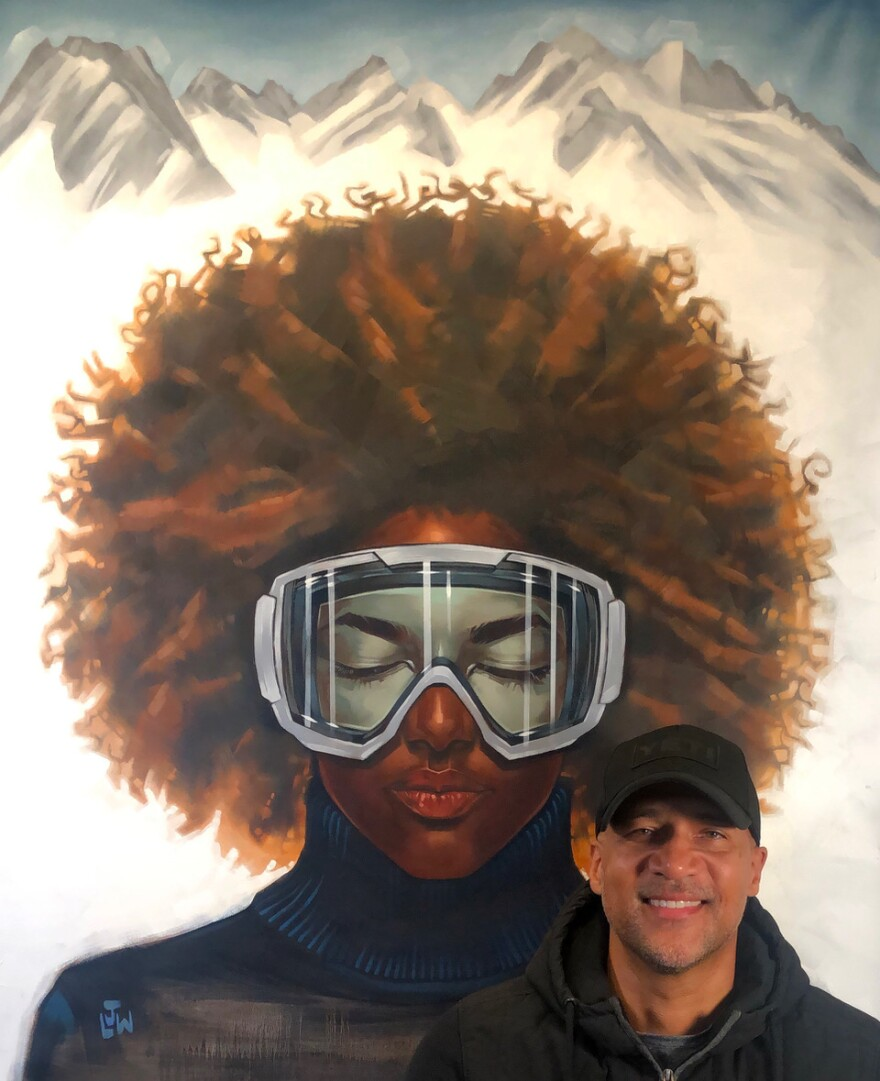 A photo of Lamont White next to one of his art works.