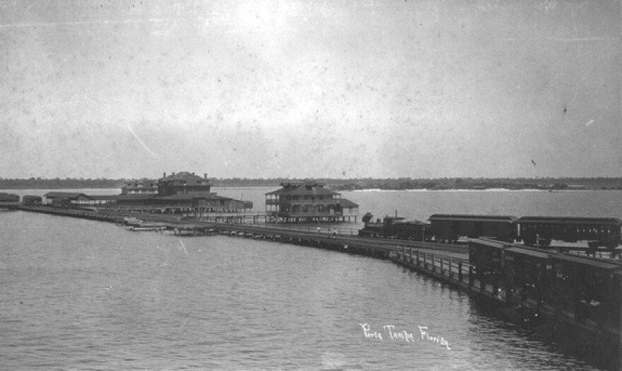 Photograph of Port Tampa, Florida, focusing on the pier, including railroad tracks. Two freight trains sit on the tracks, and three people stand on the pier.