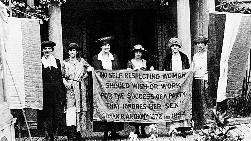 Chairwoman Alice Paul, second from left, and officers of the National Woman's Party hold a banner with a Susan B. Anthony quote in front of the NWP headquarters in Washington, D.C., in June 1920.
