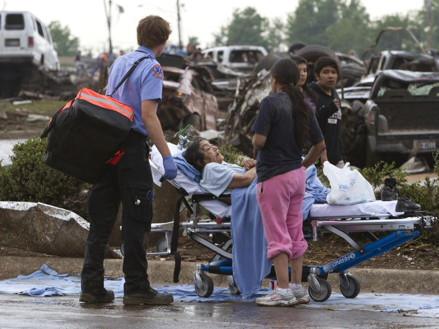 A Moore Medical Center patient sits in the parking lot after a tornado damaged the hospital  on Monday.