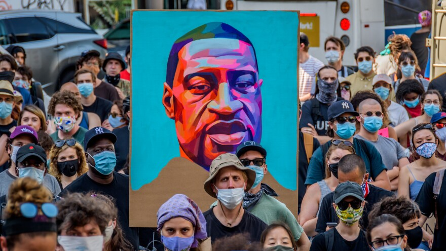"Protesters hold a portrait of George Floyd at a demonstration against police brutality in New York City. Policing ""wasn't always this big. It wasn't always this bureaucratic,"" journalist Jamiles Lartey says."