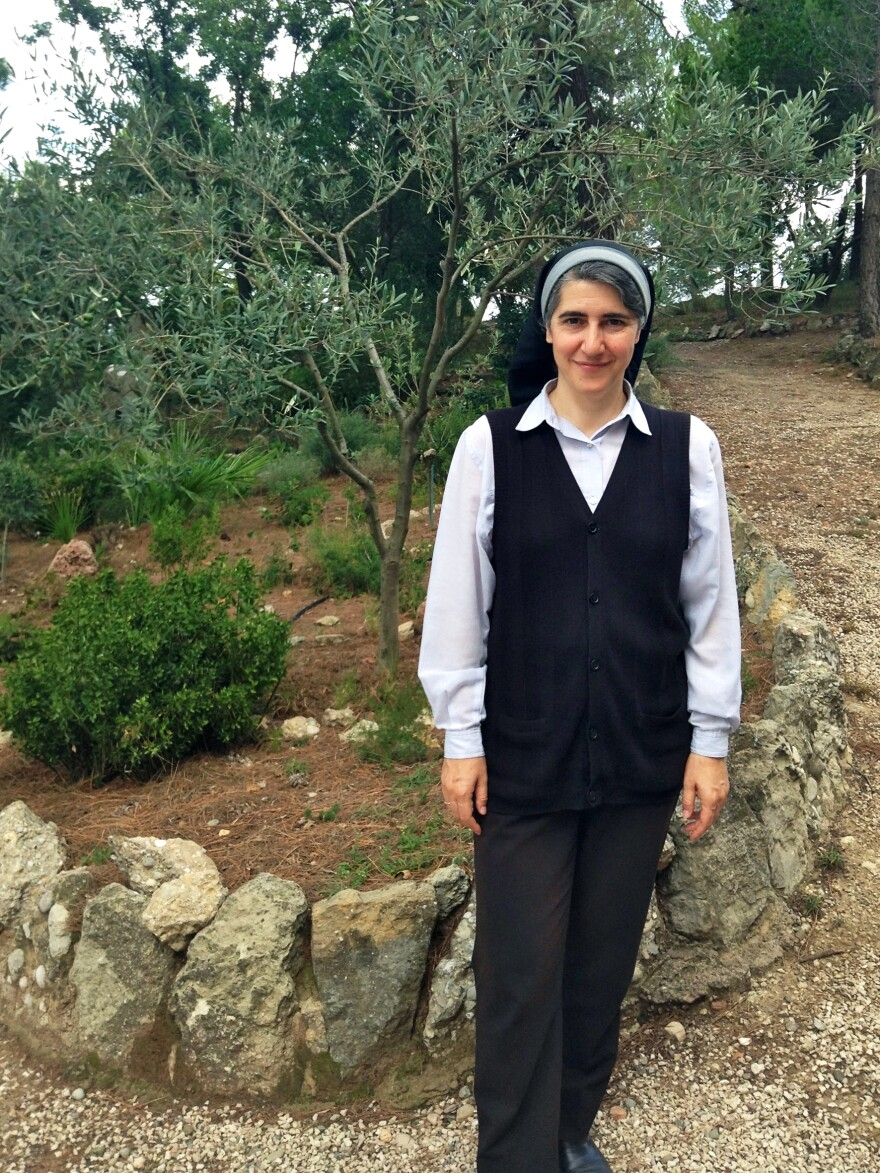 Sister Teresa Forcades stands in front of an olive tree she planted on Jan. 1, 1997 — the day she took her vows to become a Benedictine nun. Back then, the tree was just a sapling, but it has matured during her 17 years at the monastery and now bears fruit.