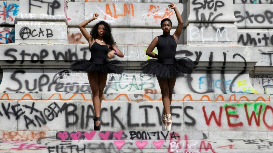 Ballerinas Kennedy George, 14, and Ava Holloway, 14, pose in front of a monument of Confederate general Robert E. Lee after Virginia Governor Ralph Northam ordered its removal after widespread civil unrest following the death in Minneapolis police custody of George Floyd, in Richmond, Va., on June 5.