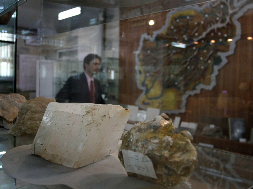 A journalist walks by an exhibit of minerals on the way to a news conference by the Afghan minister of mines, in Kabul in 2010.
