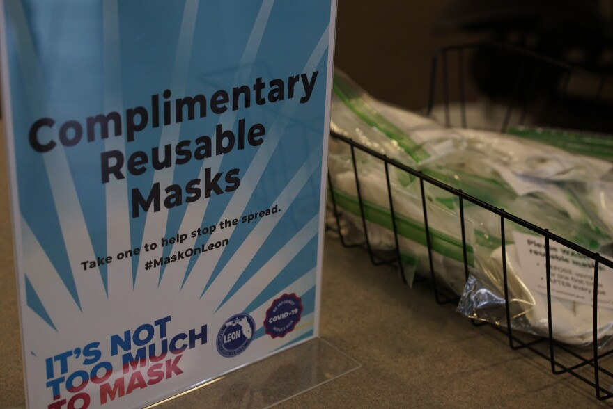 "On the counter is a sign that reads, ""Complimentary Reusable Masks. Take one to help stop the spread #MaskOnLeon. It's Not Too Much To Mask."" Beside the sign is a bin containing reusable fabric masks individually placed in Ziploc bags."