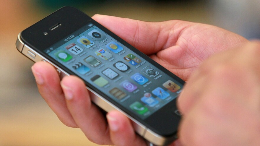 <p>An Apple Store customer looks at the new Apple iPhone 4S on Oct. 14 in San Francisco.</p>