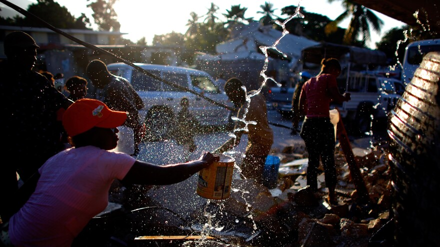 People gather around broken water pipes to collect drinking water in Port-au-Prince, Haiti, after the January 2010 earthquake.