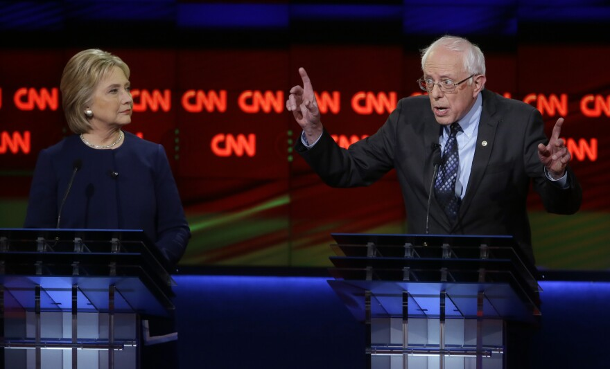 Vermont Sen. Bernie Sanders argues a point as former Secretary of State Hillary Clinton listens during the Democratic presidential debate at the University of Michigan, Flint on Sunday.