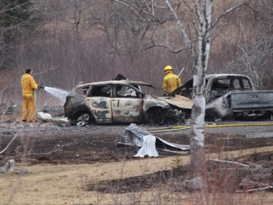 A volunteer firefighter douses hot spots near destroyed vehicles linked to the deadly weekend shooting rampage in Nova Scotia, on Monday.